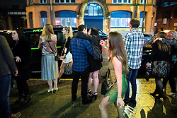 """© Licensed to London News Pictures . 17/12/2016 . Manchester , UK . A couple embrace as they queue for a taxi , on Deansgate Locks . Revellers out in Manchester City Centre overnight during """" Mad Friday """" , named for being one of the busiest nights of the year for the emergency services in the UK . Photo credit : Joel Goodman/LNP"""