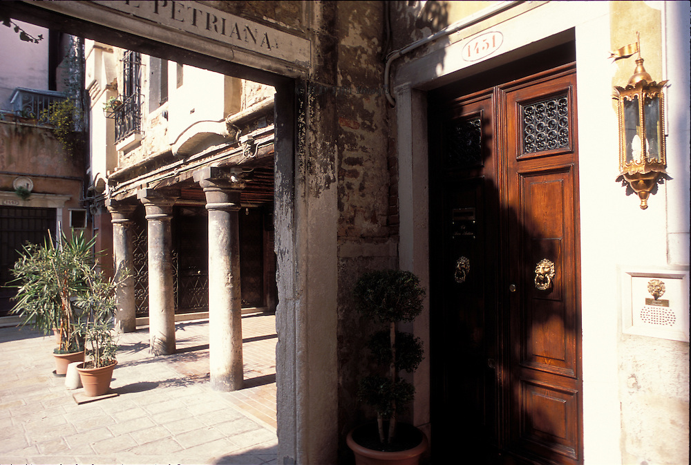 View into Corte Petriana from doorway of Ca Arco Antico on a sunny day..