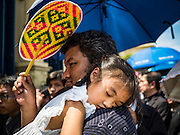 14 OCTOBER 2016 - BANGKOK, THAILAND:  A man holds his daughter while they wait in line in front of the Sahathai Samakom Pavilion at the Grand Palace in Bangkok to pay respects to Bhumibol Adulyadej, the King of Thailand, who died Oct. 13, 2016. He was 88. His death comes after a period of failing health. With the king's death, the world's longest-reigning monarch is Queen Elizabeth II, who ascended to the British throne in 1952. Bhumibol Adulyadej, was born in Cambridge, MA, on 5 December 1927. He was the ninth monarch of Thailand from the Chakri Dynasty and is known as Rama IX. He became King on June 9, 1946 and served as King of Thailand for 70 years, 126 days. He was, at the time of his death, the world's longest-serving head of state and the longest-reigning monarch in Thai history.   PHOTO BY JACK KURTZ