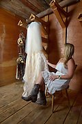 Bride with wedding gown hanging in a room with saddles.
