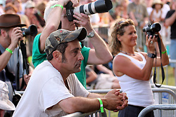 April 27 2007. New Orleans, Louisiana. <br /> The New Orleans Jazz and Heritage Festival. <br /> Lee Celano of Reuters checking out Lucinda Williams at the Gentilly Stage.<br /> Photo credit; Charlie Varleyvarleypix.com