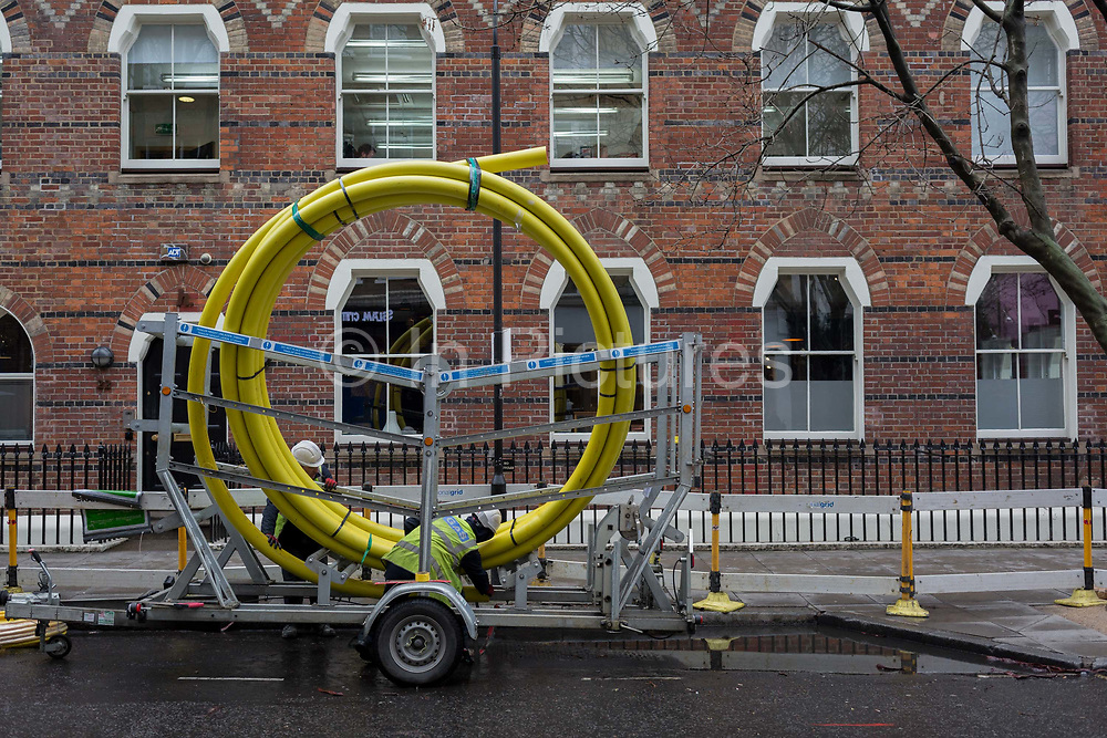 A gas contractor uncoils piping collars from a giant reel, on 28th February 2017, in London, England.