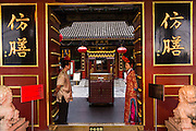 Dressed in traditional Chinese costume attendants at the Fangshan Imperial Restaurant welcome customers at Beihai Park in Beijing, China