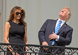 United States President Donald J. Trump, right, looks skywards as he prepares look at the partial eclipse of the sun from the Blue Room Balcony of the White House in Washington, DC, USA, on Monday, August 21, 2017. Photo by Ron Sachs/CNP/ABACAPRESS.COM