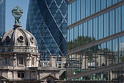 Varied ages of corporate offices including the modern Gherkin and the rotunda of Electra House, on 15th August 2016 in the City of London, UK. With the early 20th century architecture of the dome on the left 1902, the Gherkin at 30 St Mary Axe 2004 plus a less distinctive addition to the skyline on the right, we see a hundred years of building in the heart of the capital, known as the Square Mile, founded by the Romans in the 1st Century.