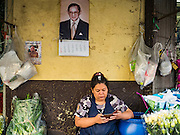 """11 AUGUST 2016 - BANGKOK, THAILAND: A vendor checks her smart phone in Pak Khlong Talat. Pak Khlong Talat (literally """"the market at the mouth of the canal"""") is the best known flower market in Thailand. It is the largest flower market in Bangkok. Most of the shop owners in the market sell wholesale to florist shops in Bangkok or to vendors who sell flower garlands, lotus buds and other floral supplies at the entrances to temples throughout Bangkok. There is also a fruit and produce market which specializes in fresh vegetables and fruit on the site. It is one of Bangkok's busiest markets and has become a popular tourist attraction.         PHOTO BY JACK KURTZ"""