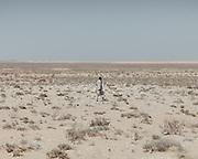 A boy walks in the desert south of El Alamein.