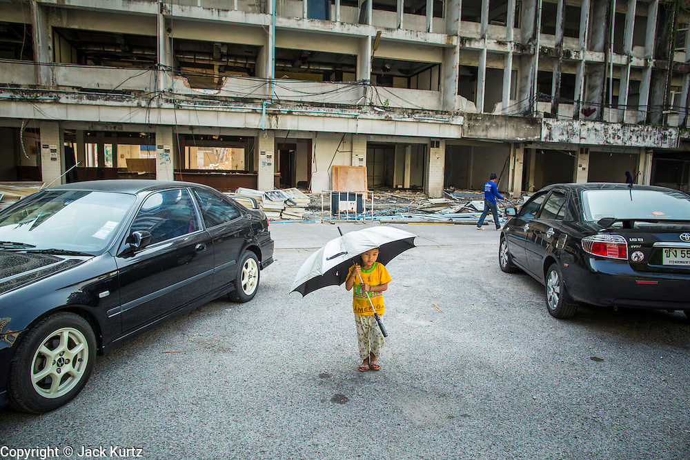 """11 DECEMBER 2012 - BANGKOK, THAILAND:  A child plays among late model cars parked in """"Washington Square"""" a notorious entertainment district off Sukhumvit Soi 22 in Bangkok. Demolition workers on many projects in Thailand live on their job site tearing down the building and recycling what can recycled as they do so until the site is no longer inhabitable. They sleep on the floors in the buildings or sometimes in tents, cooking on gas or charcoal stoves working from morning till dark. Sometimes families live and work together, other times just men. Washington Square was one of Bangkok's oldest red light districts. It was closed early 2012 and is being torn down to make way for redevelopment.    PHOTO BY JACK KURTZ"""