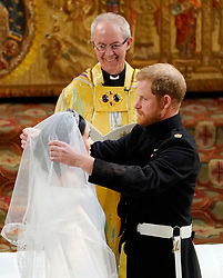 """File photo dated 19/05/18 of the Duke and Duchess of Sussex in St George's Chapel at Windsor Castle during their wedding service, conducted by the Archbishop of Canterbury Justin Welby. The royal couple have announced they are to """"step back"""" as senior members of the royal family and will now divide their time between the UK and North America."""