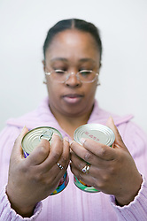Woman reading the labels on tin cans to weigh up contents,