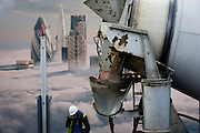 Cement mixer lorry and construction workman beneath a property developer's billboard showing a large aerial image of London skyscrapers in low cloud.