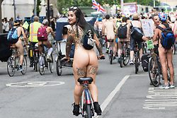 Westminster Bridge, London, June 11th 2016. Hundreds of naked and semi-naked cyclists participate in the World Naked Bike Ride that takes place in cities around the world, to highlight the alternatives to hydrocarbon fuels. PICTURED: A woman gives a cheeky smile for the camera.