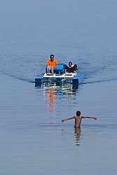 Boy Swimming To Friends Boat