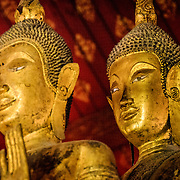 The faces of some of the Buddha statues at Wat Mai Suwannaphumaham.  Wat Mai, as it is often known, is a Buddhist temple in Luang Prabang, Laos, located near the Royal Palace Museum. It was built in the 18th century and is one of the most richly decorated Wats in Luang Prabang.