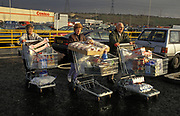 Three shoppers push their laden trolleys across the car park of the wholesale retailer, Costco Supermarket Club, on 1st November 1993, in London, England. Costco Wholesale Corporation, also known as Costco, is an American multinational corporation which operates a chain of membership-only warehouse clubs.