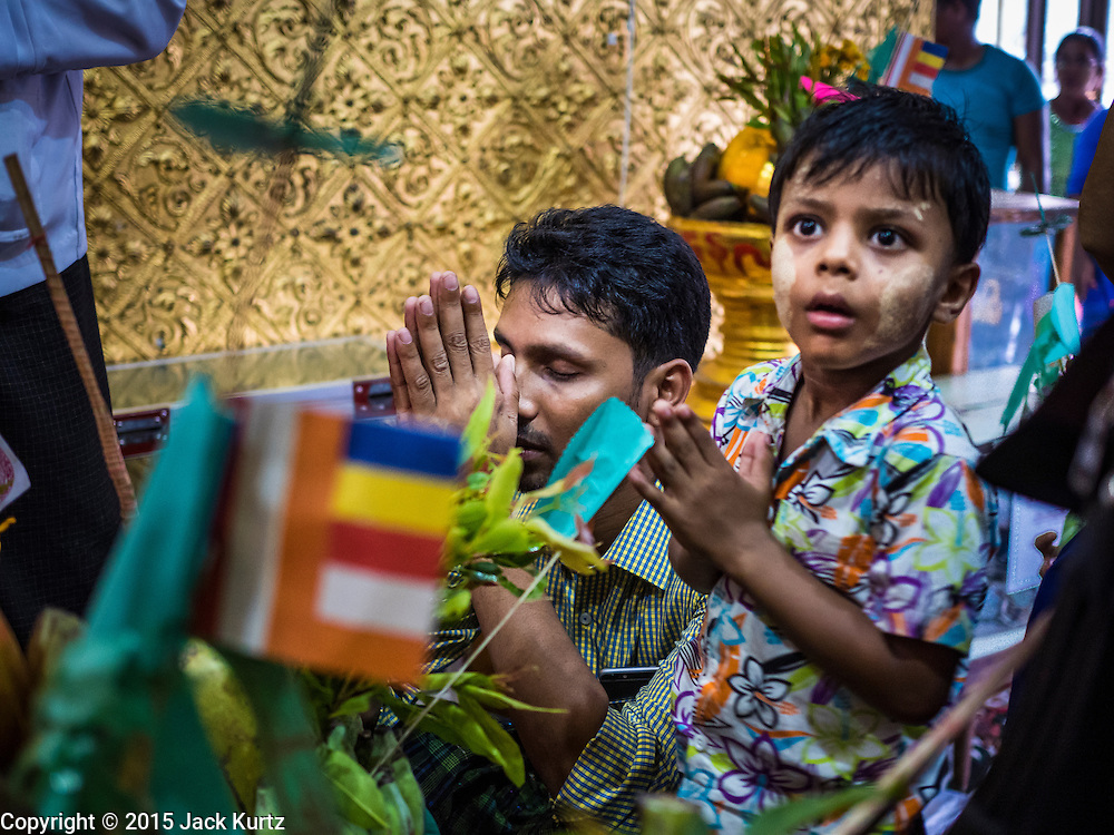 28 OCTOBER 2015 - YANGON, MYANMAR: A man and his son pray during observances of Thadingyut at Botataung Pagoda in Yangon. Botataung Pagoda was first built by the Mon, a Burmese ethnic minority, around the same time as was Shwedagon Pagoda, over 2500 years ago. The Thadingyut Festival, the Lighting Festival of Myanmar, is held on the full moon day of the Burmese Lunar month of Thadingyut. As a custom, it is held at the end of the Buddhist lent (Vassa). The Thadingyut festival is the celebration to welcome the Buddha's descent from heaven.    PHOTO BY JACK KURTZ