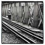 Vietnamese woman cross the long bien bridge. She wears a conic hat and carries a bag full of small breads. Repetition of metallic structure gives a graphical dynamic