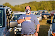12 SEPTEMBER 2020 - DES MOINES, IOWA: MICHAEL RAMIREZ stands next to his car with his hand over his heart during the Pledge of Allegiance at the Polk County Democrats Steak Fry in Waterworks Park in Des Moines. The Steak Fry is the largest fundraiser of the year for Polk County Democrats. This year nearly 1,000 people attended. The Steak Fry observed public health guidelines. Normally the Steak Fry is a picnic but this year people stayed in their cars while meals were brought to them and they wore masks when they were outside of the cars. Most of the speakers appeared via online speeches.     PHOTO BY JACK KURTZ