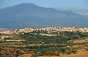 The town of Regalbuto on a hilltop with the peak of the volcano Mount Etna in the distance.