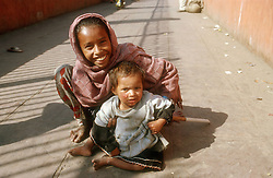 Two young children sitting in street in Delhi; India,