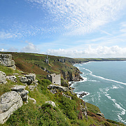 Wheal Trewavas Mine is at Rinsey near Porthleven. It is on the southern end of the granite outcrop known as the Godolphin-Tregonning Granite<br /> <br /> 1834 Wheal Trewavas opened. A plan of the time shows four copper lodes and one tin lode. The south east copper lode continued out under the sea and a small pumping engine and a steam whim were built on the south lode. Ore was carried to the cliff top by a horse whim. The sett of Wheal Trewavas contains four main copper lodes running generally in a NW-SE direction. They are North Lode; Sowan Way Lode; Trewavas South (or Old) Lode and Nimble Cutter Lode. These are intersected by the Great Tin lode running east to west across them. A pumping engine was installed on Old Engine shaft working the Old (South) Lode.<br /> <br /> 1838 a new pumping engine house housing a 45-inch cylinder was erected a few hundred metres to the east -on slightly higher ground - over New Engine (or Rogers') shaft.<br /> <br /> 1846 Wheal Trewavas closed. There was a suspicion that the dividends were being paid out of bank overdrafts.<br /> <br /> 1840's the mine employed around 200 people in mining and ancillary trades at Wheal Trewavas. A new shaft was sunk on the eastern section of the sett with a 70-inch pumping engine replacing the smaller engine on New Engine Shaft. This new shaft known as Diagonal shaft reached a depth of nearly 600 feet in the mid 1840'sl. It is known to have employed about 160 people around about this time.<br /> <br /> In the years Wheal Trewavas was in operation it produced over £100,000 worth of copper ore.<br /> <br /> The two engine houses still exist as the remains of Wheal Trewavas A circular flat area beyond the boiler house is one of Cornwall's best surviving 'manual capstan plats' and it is regularly used by helicopter pilots from Culdrose for landing practice.