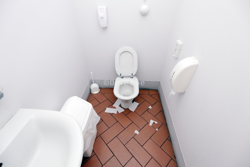 public toilet with paper laying around the pot