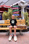 11 year old child sitting outside Bubba Gump restaurant in Kailua-Kona. Big Island, Hawaii