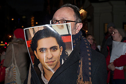 © Licensed to London News Pictures. 22/01/2015. Saudi Arabian Embassy, London, UK. A man with a photo of Raif Badawi outside the Saudi Arabian Embassy in London on 22 January 2015 to attend the vigil for Raif Badawi, a Saudi Arabian blogger and editor, who has been sentenced to 10 years in prison as well as a punishment of 1,000 lashes, to be delivered in 20 flogging sessions.  The second planned flogging is to be suspended after a medical committee assessed that he should not undergo a second round of lashes on health grounds. Photo credit : Stephen Chung/LNP