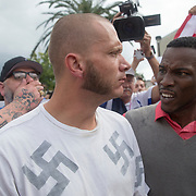 A lone white supremacist walks through the crowd with blood flowing from his mouth as protestors gather in the staging site prior to a Richard Spencer speech at the Phillips Center for the Performing Arts on the University of Florida campus in Gainesville, Florida on Thursday, October 18, 2017. (Alex Menendez)