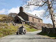 Farmer driving quad bike past village church, Buttermere, Cumbria, England, UK