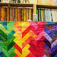 072114  Adron Gardner/Independent<br /> <br /> Lynn Olinger raises a rainbow colored quilt at the Gallup Service Mart Monday. The quilt, along with many others will be part of a silent auction held for  Lisa Byker, a mother of four kids who has been diagnosed with a brain tumor.