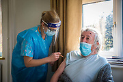 An elderly patient receiving the COVID-19 vaccination as part of a home visiting service for housebound patients from Dr Fordham of the Channel Health Alliance at their home in the community outside Dover to administer the COVID-19 Vaccination on the 27th of February 2021, Dover, Kent, United Kingdom.