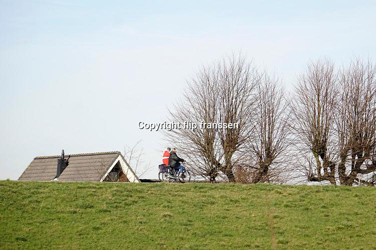 Nederland, Eldik, 14-2-2019Mensen, ouderen, maken een fietstochtje over de dijk langs de Waal, Rijn . Het is een mooie dag met zon en een blauwe onbewolkte lucht. FOTO: FLIP FRANSSEN