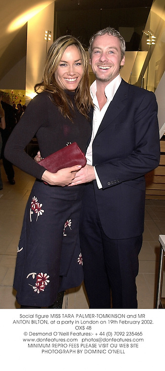 Social figure MISS TARA PALMER-TOMKINSON and MR ANTON BILTON, at a party in London on 19th February 2002.OXS 48