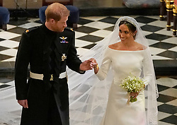 """File photo dated 19/05/18 of the Duke and Duchess of Sussex as they leave St George's Chapel at Windsor Castle following their wedding service, conducted by the Archbishop of Canterbury Justin Welby. The royal couple have announced they are to """"step back"""" as senior members of the royal family and will now divide their time between the UK and North America."""