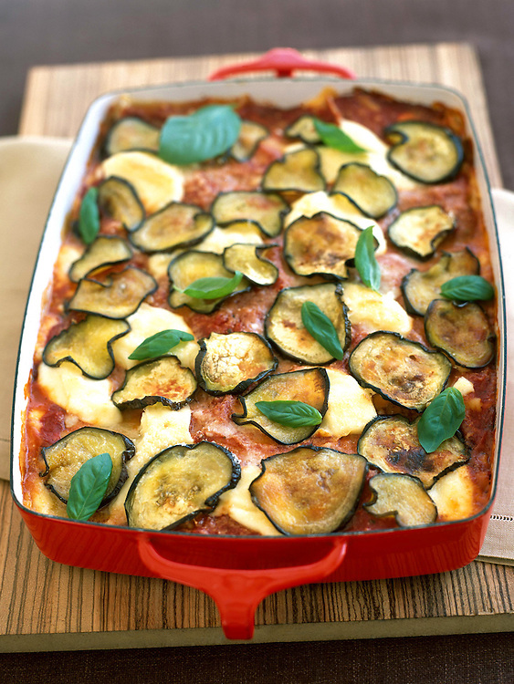 baked lasagna in red pan with eggplant slices and basil leaves