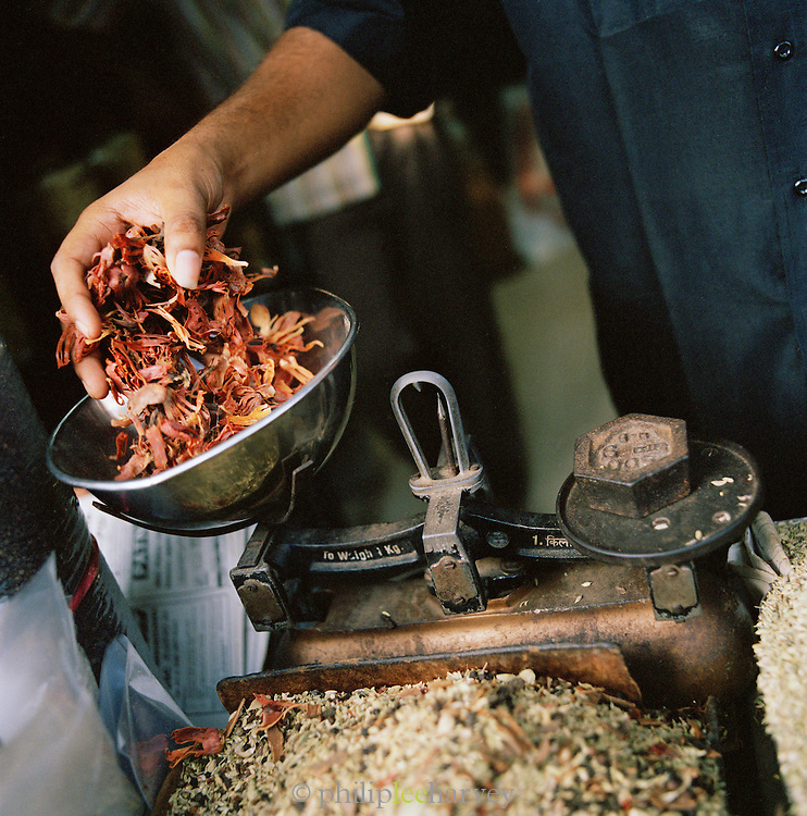 Dried flowers being weighed at local market, Cochin, Kerala, India