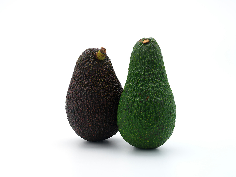 two whole avocados on a white background