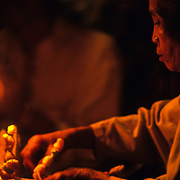 Woman lights candles during Basi ceremony, Ban Pak Ou, Luang Phrabang, Laos