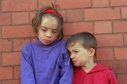 Young girl and boy standing together looking distressed,