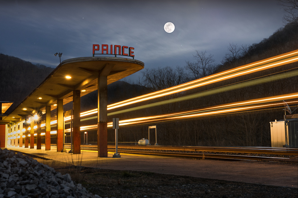 A train passes the old Amtrak station in the small town of Prince, West Virginia, one of the few remaining towns located within the New River Gorge, as the full moon rises high above the mountains.