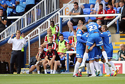 Peterborough United's Britt Assombalonga celebrates scoring the opening goal of the game with team-mates next to a dejected Swindon Town manager Mark Cooper - Photo mandatory by-line: Joe Dent/JMP - Tel: Mobile: 07966 386802 03/08/2013 - SPORT - FOOTBALL -  London Road Stadium - Peterborough -  Peterborough United v Swindon Town - Sky Bet One