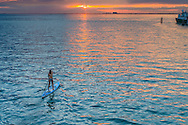 A young woman paddles toward the setting sun in Bear Cut between Virginia Key and Key Biscayne, Florida. <br /> <br /> WATERMARKS WILL NOT APPEAR ON PRINTS OR LICENSED IMAGES.<br /> <br /> Licensing: https://tandemstock.com/assets/99056672
