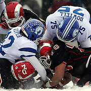 Darien quarterback Silas Wyper, (twelve), loses possession of the ball as he is sacked by Cole Harris, New Canaan, as during the New Canaan Rams Vs Darien Blue Wave, CIAC Football Championship Class L Final at Boyle Stadium, Stamford. The New Canaan Rams won the match in snowy conditions 44-12. Stamford,  Connecticut, USA. 14th December 2013. Photo Tim Clayton