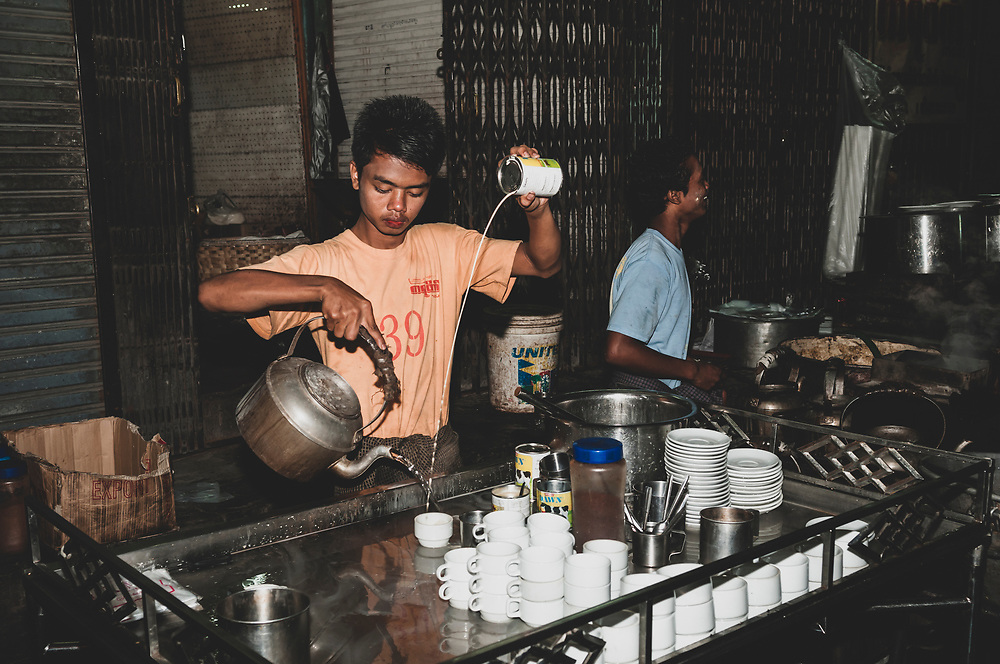 Mandalay, Myanmar - November 10, 2011: A young man at a sidewalk cafe pours hot water and condensed milk into a cup of tea. Tea is an important part of Burmese culture.
