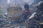 Asia, Philippines, Manilla, Smokey Mountain Rubbish dump. Child secures his basket. Thousands of poor and often indigenous people work sifting through the rubbish, recycling materials such as paper, various metal and plastic. They earn about $1 a day. The place is rife with disease.Photograph © Nigel Dickinson