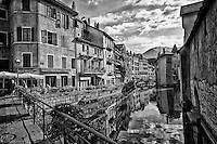 Black and white view of The French Alps, and colorful buildings taken from a bridge above the reflective waters of Thiou Canal, Old Town Annecy, France.