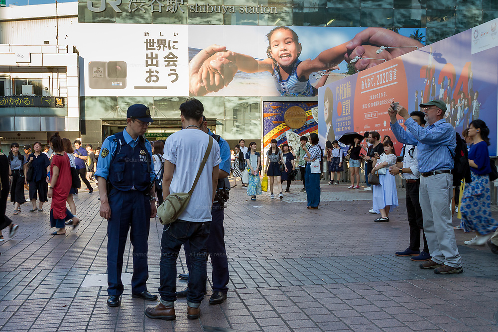 Two Japanese policemen stop and search a young Japanese man in Hachiko Square in