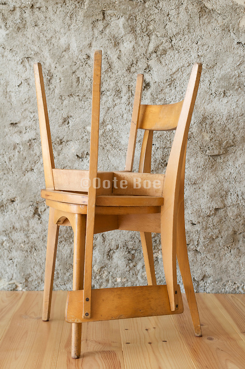 two wooden chairs one stacked on the other