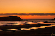 The sun is just about to disappear behind the horizon along the Oregon coast. I have been waiting for this moment for about 45 minutes, it's quite windy, but warm this summer evening. The reds and oranges are fabulous, as are the sillouettes.